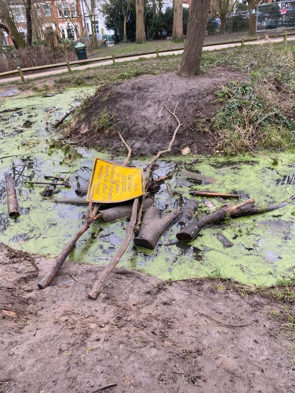 Road signs and branched dumped in Stationer Park pond. -St Lukes Vicarage, 46 Mayfield Road, London, N8 9LP