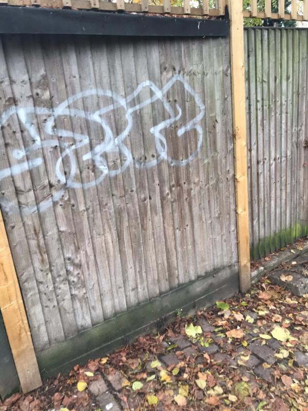 White spray painted tag is located on a wooden fence situated on Green Man Passage opposite the Children's nursery near the junction with Alexandria Road w13-34 Green Man Passage, West Ealing, London W13 0TG, UK