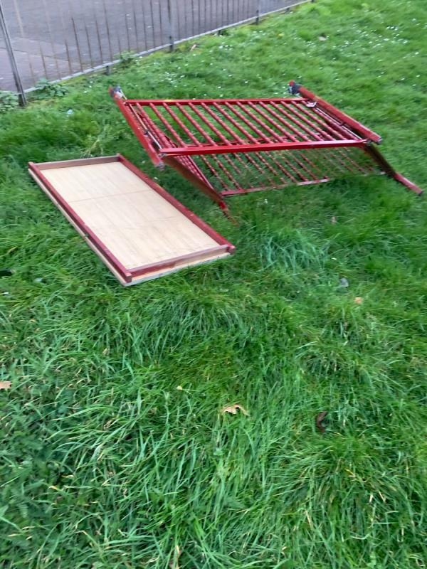 Metal bed frame and wood dumped on grass at top of morse close needs removing ASAP -24 Morse Close, London, E13 0HH
