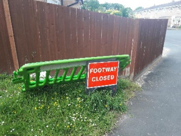 These barrier sections and sign have been left here for some 18 months or so since an SEE contractor did some repairs in the pavement at the other end of this footpath, in Pennine Way.-14 Cheviot Close, Farnborough, GU14 9HS