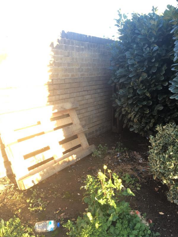 Two pallets dumped in the flower bed at entrance to West Mersea Close-43 Hanameel Street, London, E16 1UA