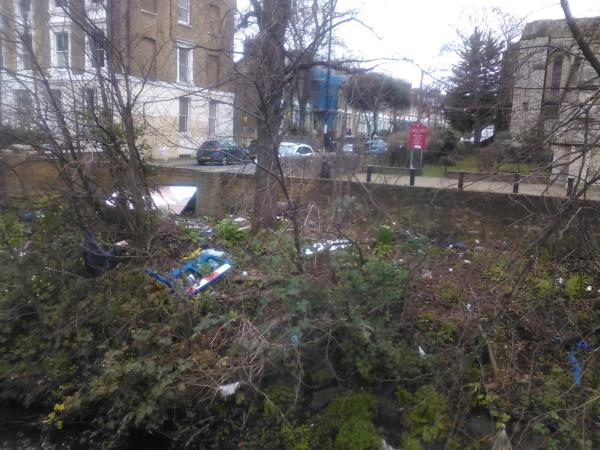 A large mirror and a plastic barrier have been left on the river bank of the River Quaggy, opposite the houses on Granville Grove.-25 Lewisham High St, London SE13 7EP, UK