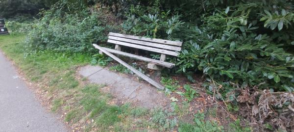 Damaged bench near pathway that goes to Queen Elizabeth Park. Bench is on side of A325.-25 Queen Victoria Court, Farnborough, GU14 8AR
