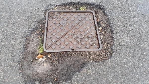 pothole around drain  cover outside number 76 downsway-21 Annington Gardens, Shoreham by Sea, BN43 5GS