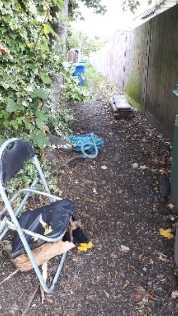 alleyway behind Elm Grove Rd on Clockhouse rd, dumped broken chair, blue rope, two large pieces of glass and a load of concrete -44e Clockhouse Road, Farnborough, GU14 7QZ