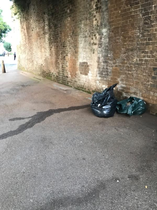 Black bags of rubbish dumped under the arches, @ junction with Stracy road-123 Woodgrange Road, London, E7 0HY