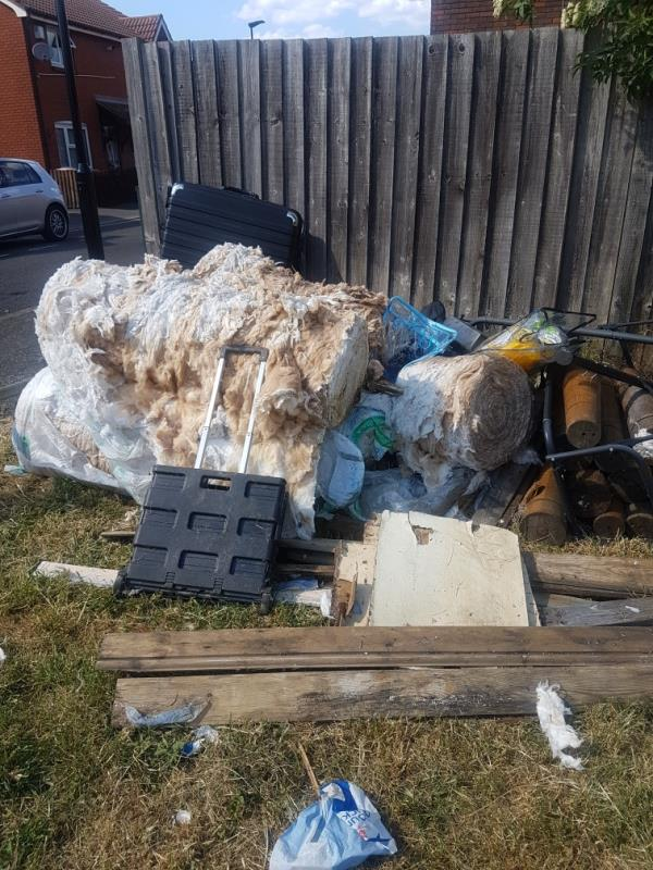 piles of insulating material, tyre, suitcase, wood and other rubbish left on grass-29 Barry Road, London, E6 5TA