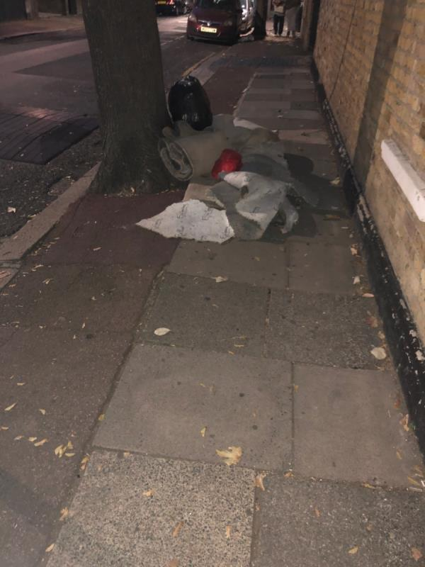 Corner of Samson street and Barking Road. Carpet blocking public footpath next to tree-655d Barking Road, Plaistow, E13 9EX