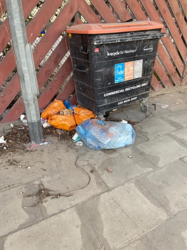 Growing pile of waste by the strangely place commercial bin under the DLR line opposite side of road the ambulance station -Silvertown Fire Station, 303 North Woolwich Road, London, E16 2BG