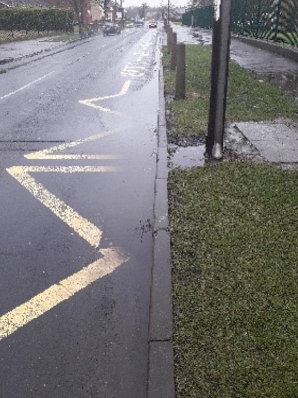 Blocked drain outside the main pedestrian access gate for Berrybrook Primary School. The water cars splash is contributing to a footpath flooding issue I am reporting on a separate report. -22 Underhill Lane, Wolverhampton, WV10 8LS