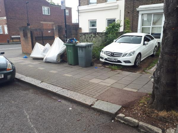 Mattresses and other refuse fly tipped on the footway in front of 67 Chobham Road. Bins permanently stored on the footway. Car illegally driven across the footway in the absence of a crossover.-73 Chobham Road, London, E15 1LX