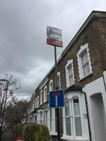 Estate agent sign and Christmas tree put at top of street signs at junction of Lavell Street and Winston Road and stickers put on pole that has Christmas tree image 1-78 Winston Road, London, N16 9LR