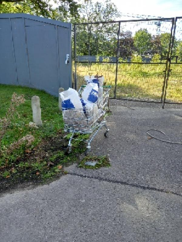 fly- tipped waste bags in trolley at the back of the library, outside the entrance to the former police station. -Farnborough Library Pinehurst Avenue, Farnborough, GU14 7JT