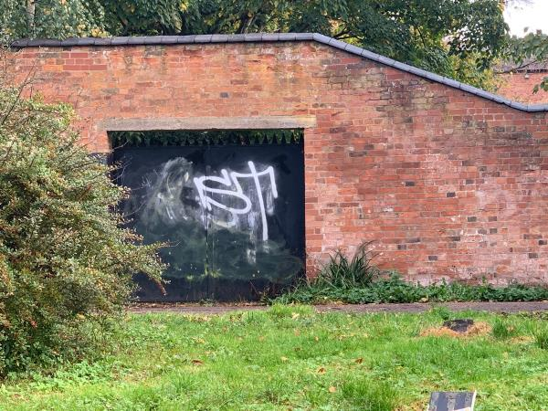 Graffiti on the exterior of walled garden Metal door and also on the wall-107 Cort Crescent, Leicester, LE3 1QL