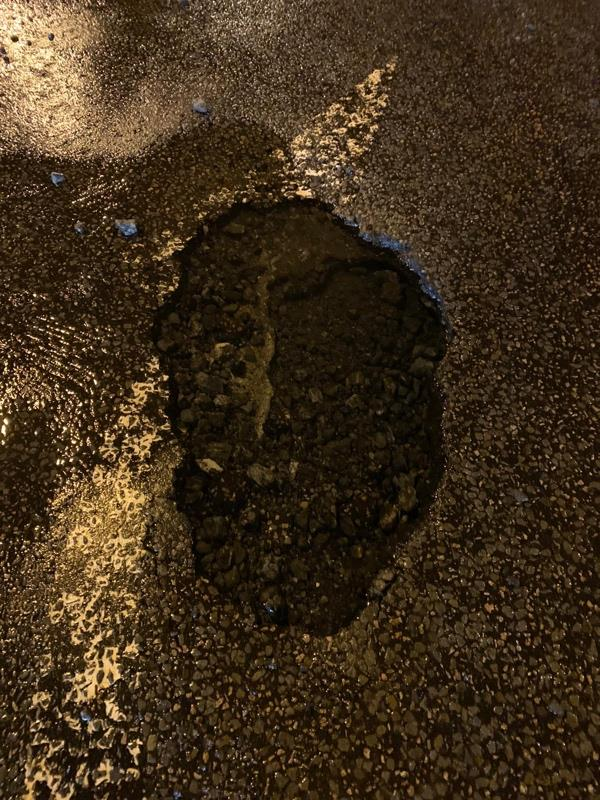 Larger than large pot hole right on the roundabout  in west street sompting-Stocks House West Street, Sompting, BN15 0BE