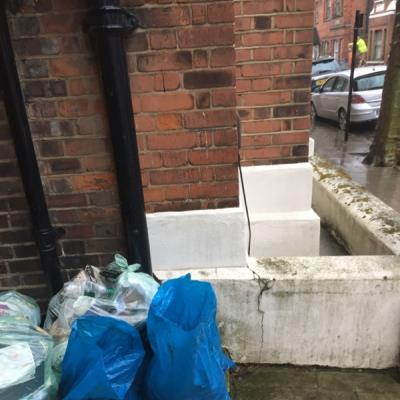 Building materials, bitumen rubble and old wooden sleepers, have been dumped alongside the recycling bags between the first two blocks  of Rowhill Mansions -152 Clarence Road, London, E5 8DY