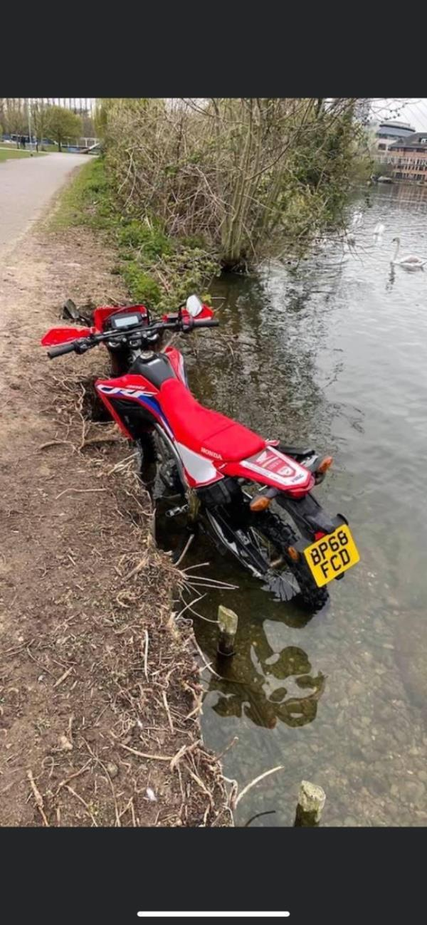 Abandoned motorcycle at edge of river in Christchurch Meadows-George Street, Reading, RG1 8DB