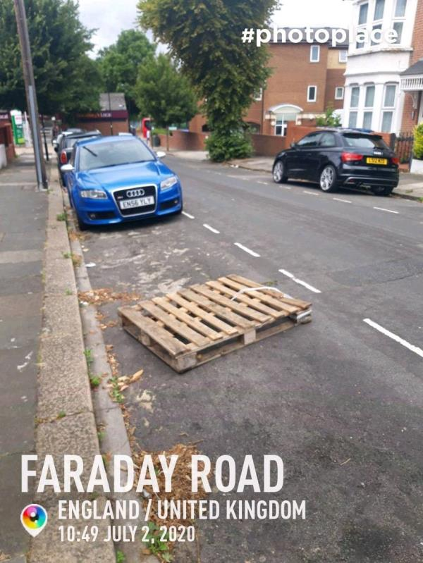 Resident left the voice main in Highway Services and reported that someone has put the wooden pallets on carriageway obstruction - outside No 12 Faraday Rd, W3 adjacent to near the kerbs -12 Faraday Road, W3