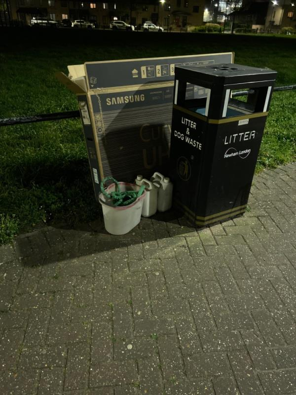Large box and various containers for cleaning products by bin on Evelyn Road on the pavement on the village green side -22 Evelyn Road, London, E16 2AR