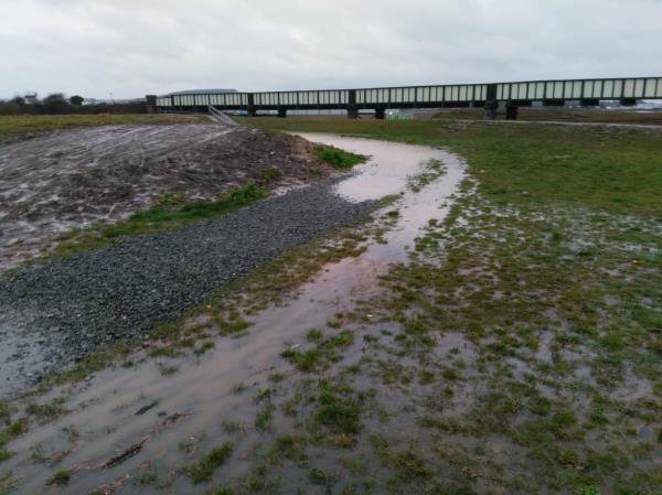 A section of this coarse gravel footpath around 50 yards long, just at the lower end of the ramped section with handrail, has been regularly flooded with 3+ inches of water for most of the time since October 2019. I realise this is a duplicate report but I wanted to add weight to the case. Many people use this path to get to/from the airport and embankment path, and without wellington boots, the path is impassable (without very wet feet). The ground around it is extremely wet and muddy (but is the only alternative) and as well as getting covered in mud splashes, presents a slipping/falling risk because the part near the handrail section is steeply banked.  Given this path was only finished a year ago, I am disappointed the path does not drain away at all -- only a sunny day helps (before it rains again). I would hope drainage could be arranged. image 1-5 Cecil Pashley Way, Shoreham by Sea, BN43 5FF