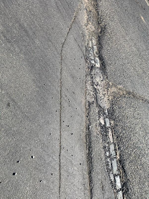 This junction into the industrial estate is hazardous. The edge of the road has a deep and dangerous 3m pothole. It is a trip hazard to pedestrians crossing, a danger to cyclists passing and damaging to cars.-Cipara Natts Lane, Billingshurst, RH14 9EZ