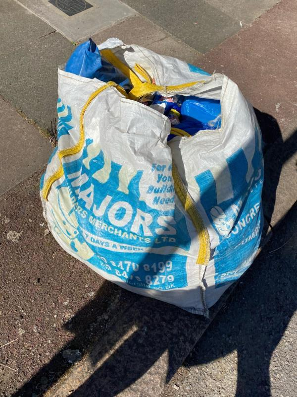 Construction waste in a large bag on pavement. It's been there weeks -27a Maryland Square, London, E15 1HF