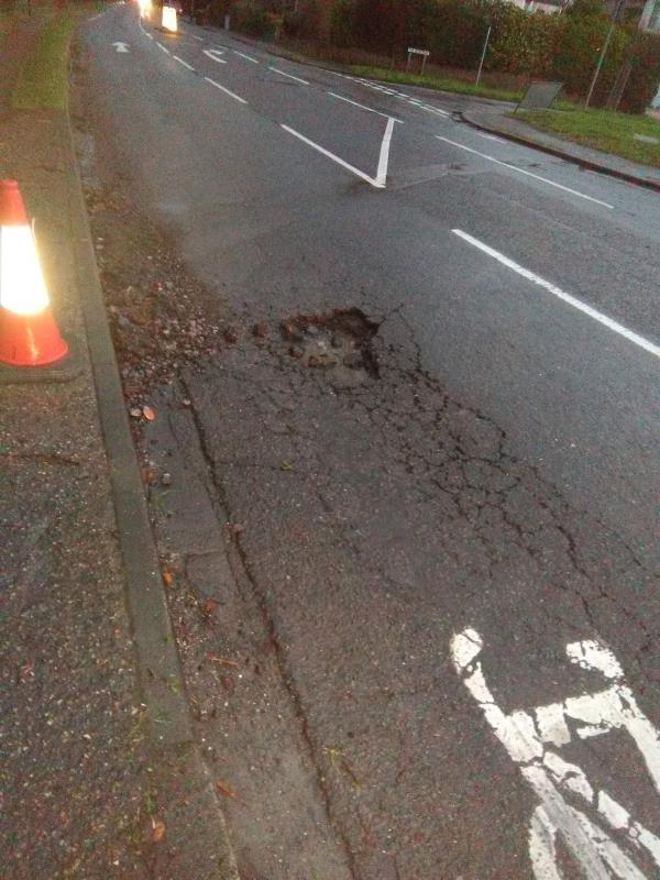 Large pothole at end of cycle lane with severe wheel track cracking/subsidence. Breaking up every time an HGV goes over it.-1 Brandy Hole Lane, Chichester, PO19 5RJ