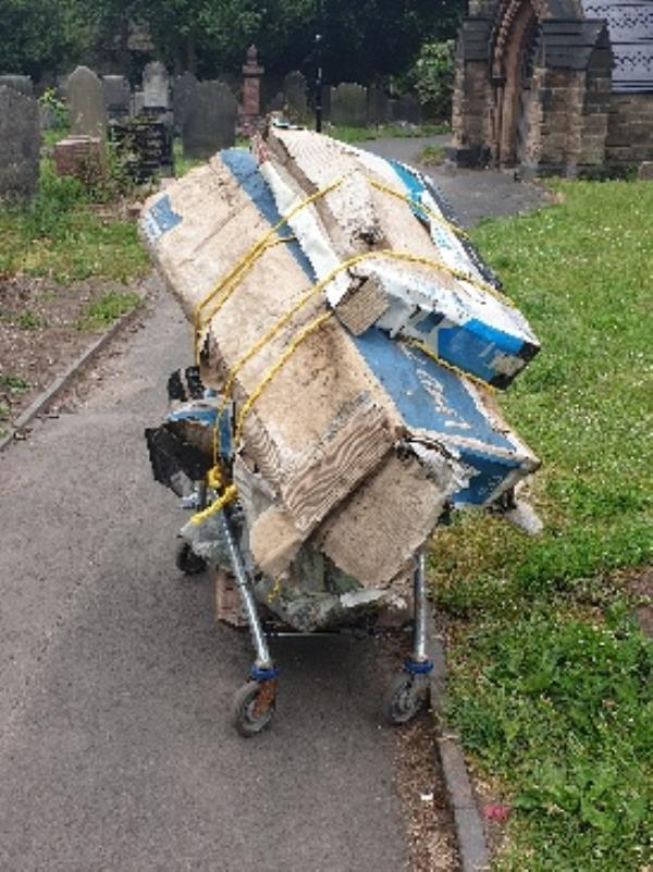 Rubbish fly tipped in the grounds of st Mary's church on path-129 Old Fallings Ln, Wolverhampton WV10 8BU, UK